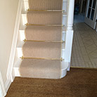 Stair rods on striped stairway carpet